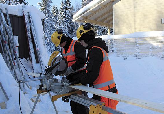 Talonrakentajaopiskelijat sahaamassa lautaa talvella