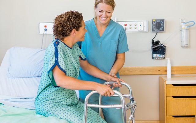 Hoitaja avustaa potilasta nousemaan sängyltä