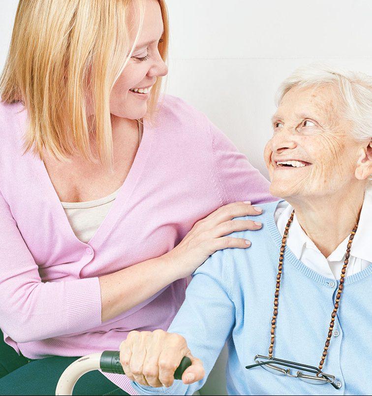 lähihoitaja istuu vanhuksen vieressä ja he hymyilevät toisilleen
