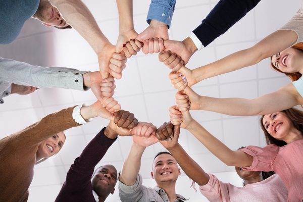 Low Angle View Of People Making Circle With Their Hands