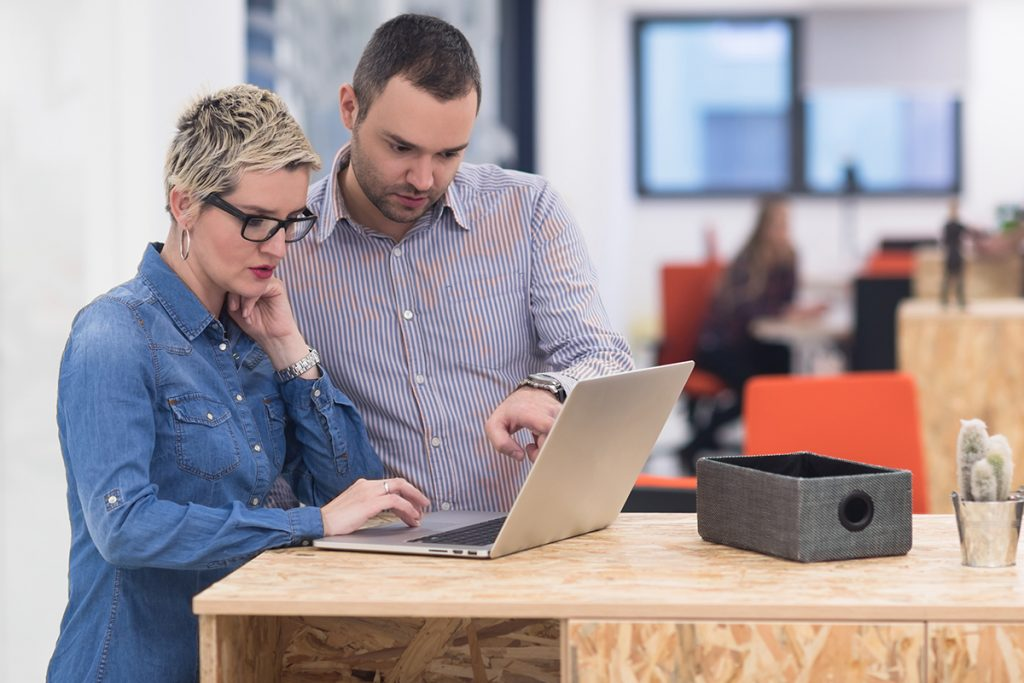mies ja nainen katsovat läppäriä toimistossa
