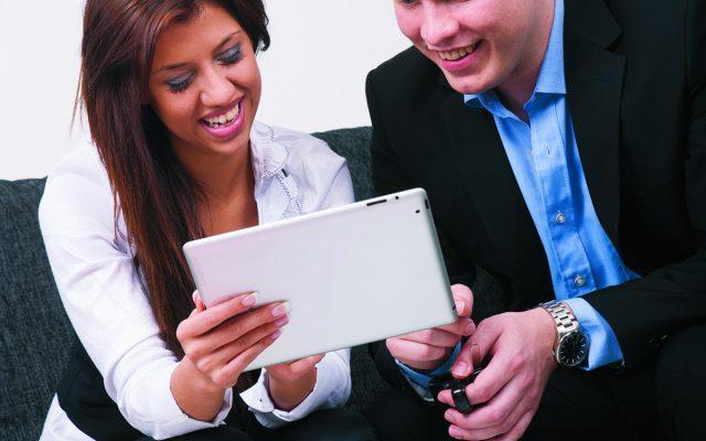 mies ja nainen istuvat sohvalla ja tutkivat papereita