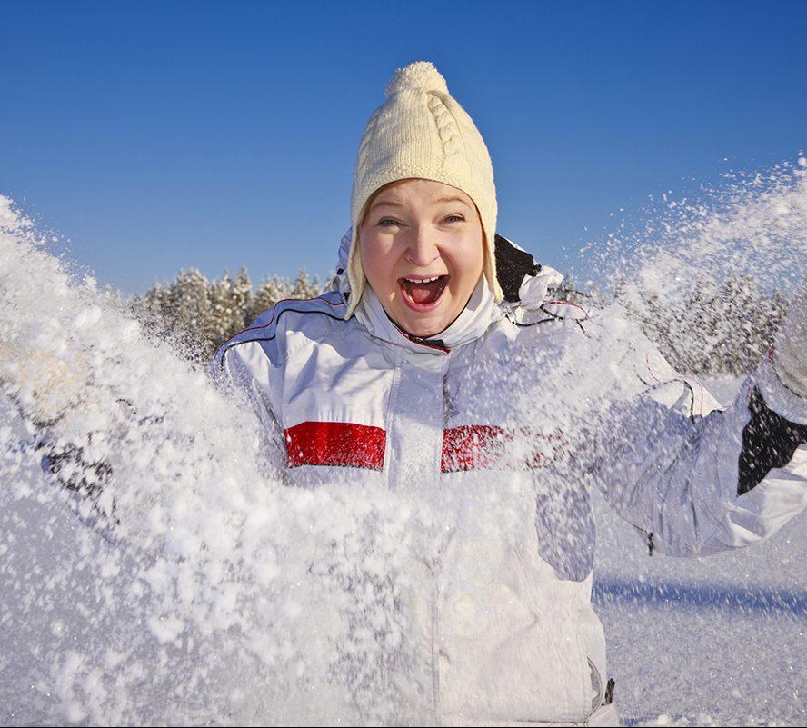 nainen nauraa ja pöllyttää lunta