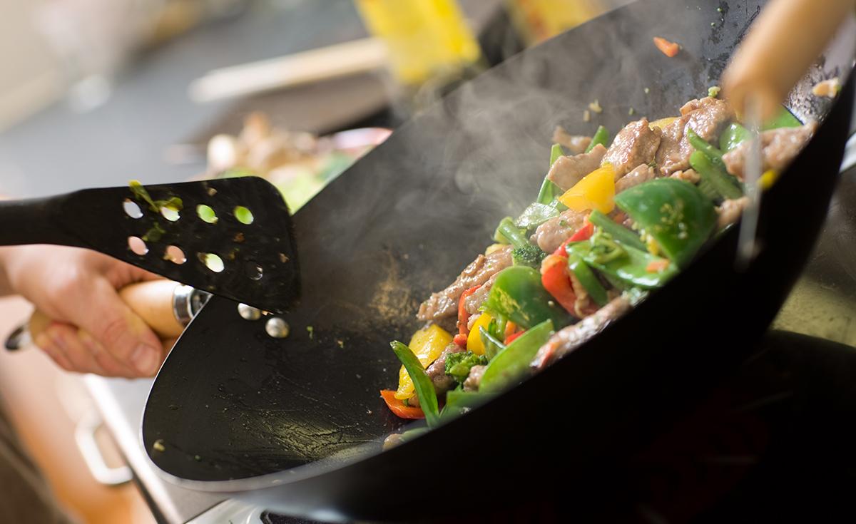 Kokki paistaa vihanneksia ja lihaa vokkipannulla