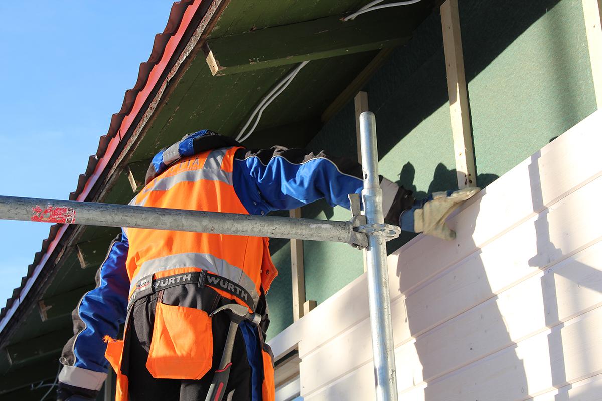 Talonrakentaja laudoittamassa talon seinustaa