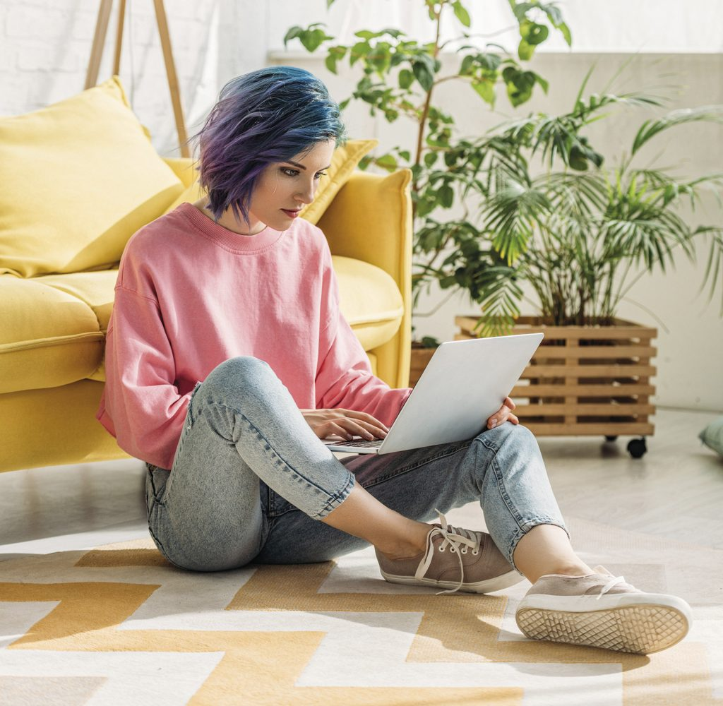 Girl with colorful hair working with laptop on floor in living room