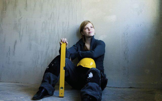 nainen istuu lattialla remonttihaalareissa ja kypärä polvella