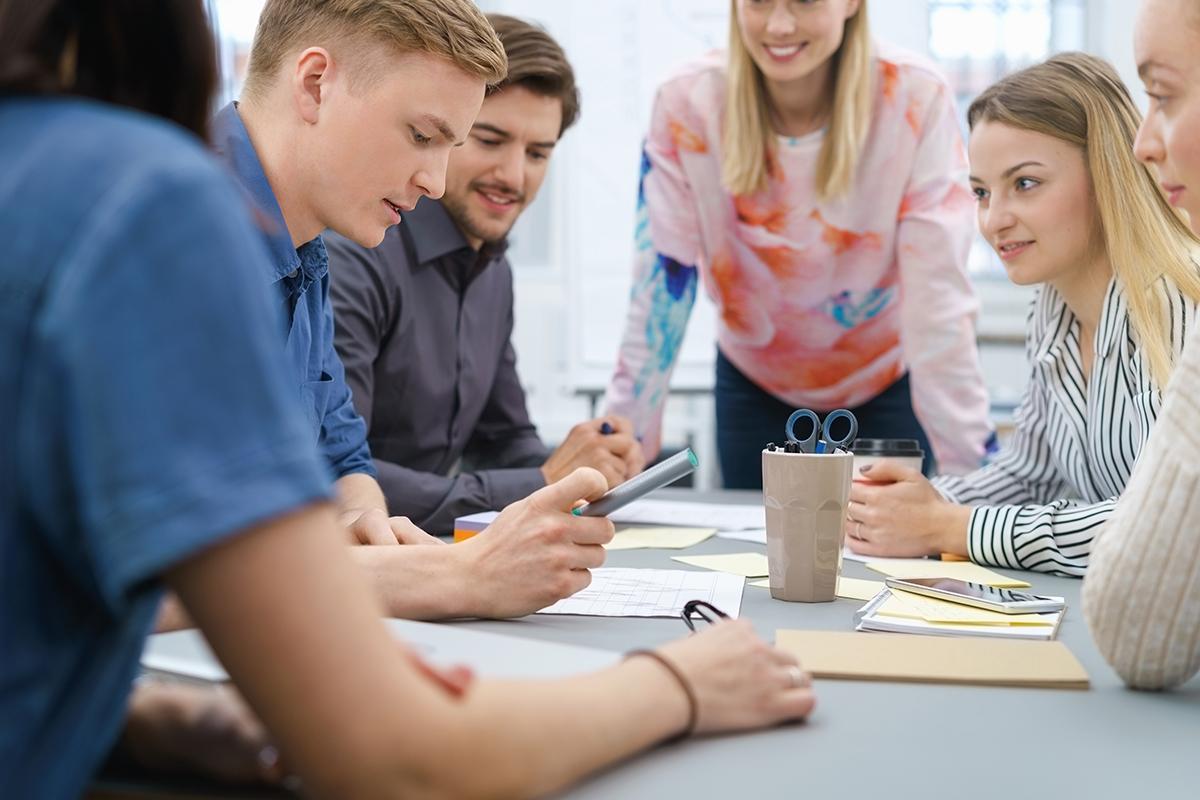 nuoria ihmisiä suunnittelemassa pöydän ääressä