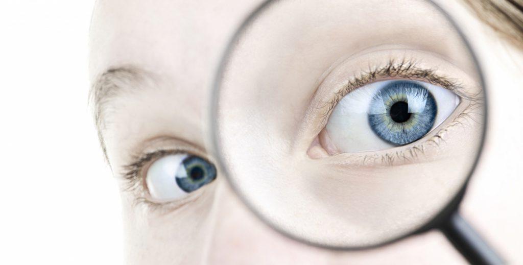 lähikuva silmästä, joka katsoo suurennuslasiin