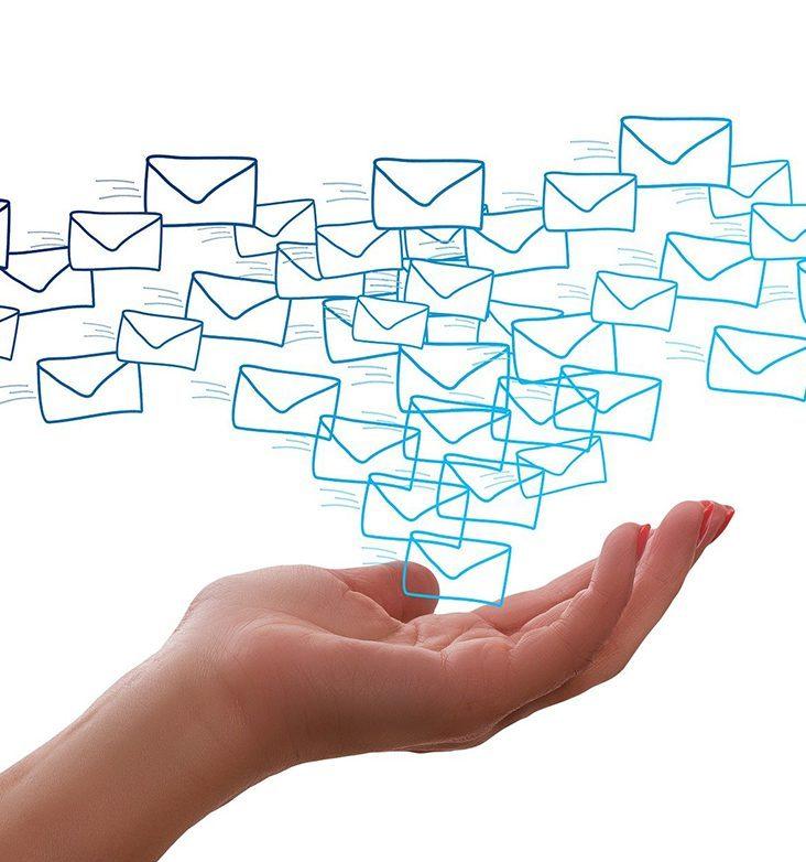 käsi, jonka yläpuolelle piirretty e-mail-kirjekuoria