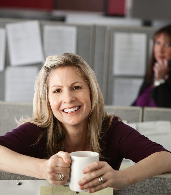 hymyilevä nainen nojaa sermiin toimistossa ja pitelee kahvikuppia