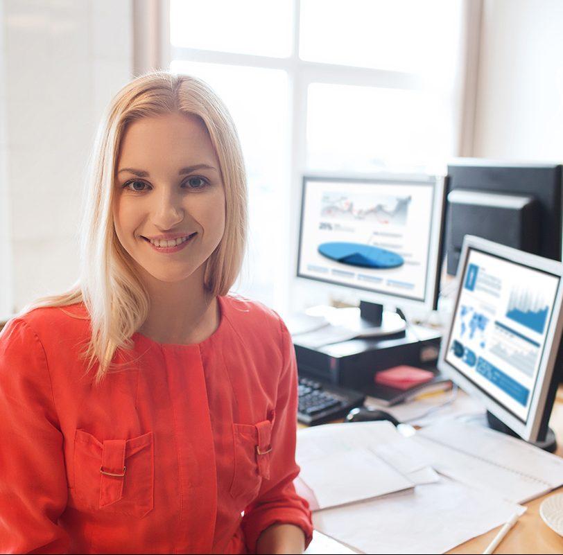 nainen istuu, takana työpöydällä tietokoneita
