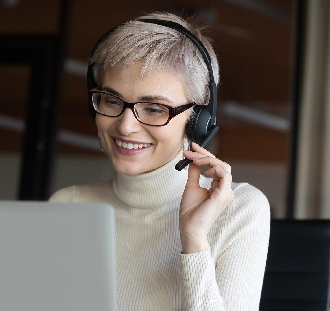 nainen hymyilee ja keskustelee etänä tietokoneyhteydellä