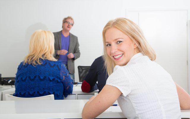 nainen katsoo olan takaa ja hymyilee oppitunnilla luokassa