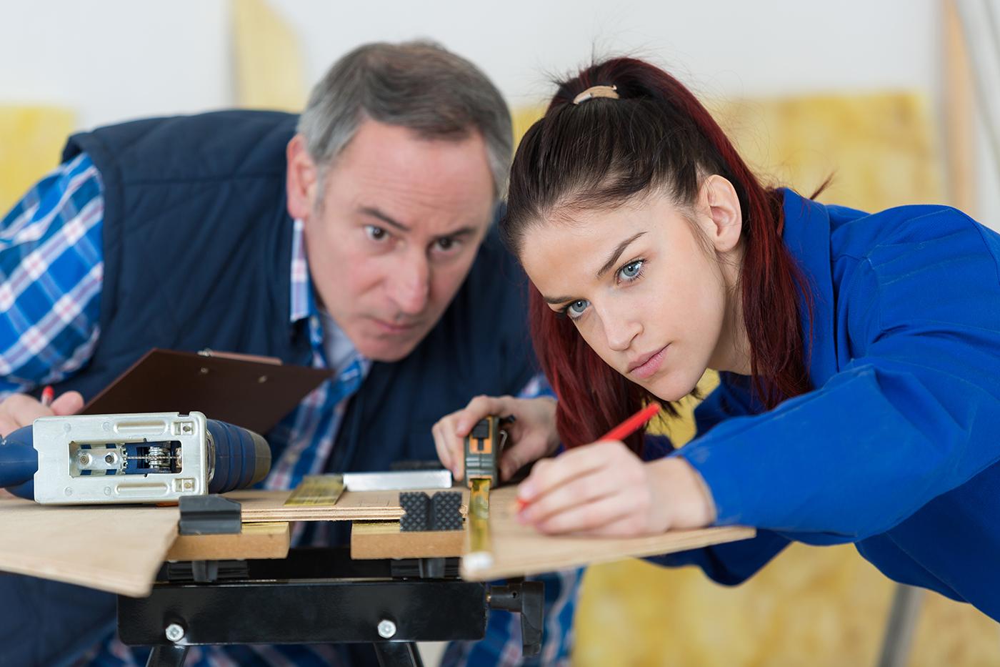 nuori naisopiskelija mittaa puupöytää ja vanhempi miesopettaja tarkkailee vierestä