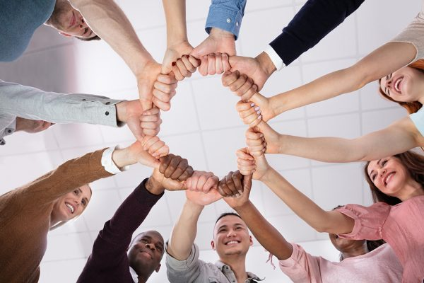Multi-ethnic Group Of People Holding Each Other Thumbs Forming Circle