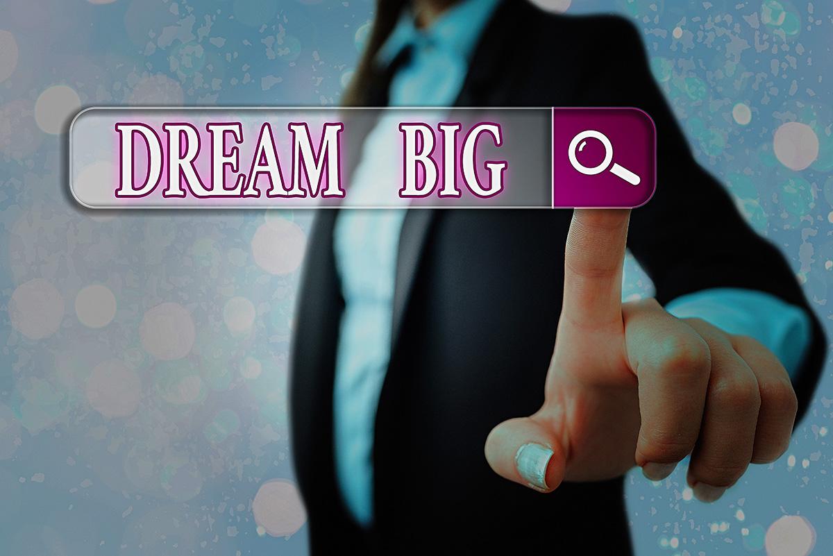nainen koskettaa ruutua, jossa lukee Dream Big