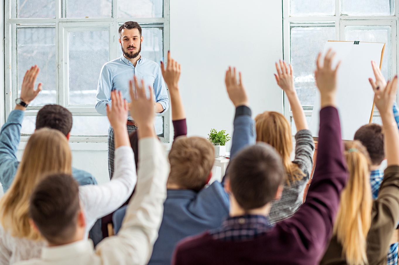 Miesopettaja kertoo opiskelijoille yrittäjyydestä ja opiskelijat viittaavat ja haluavat kysyä.