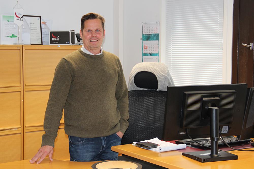 Johtaja Veikko Oljakka seisoo oman työpöytänsä takana työhuoneessaan Rönkä Oy:ssä.
