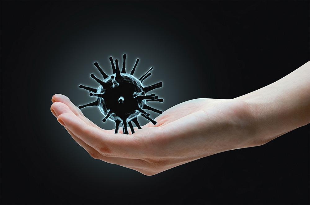 Musta tausta jossa ihmisen kämmenellä musta koronavirus.